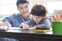 Chinese son doing homework with father — Stock Photo