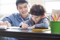 Fils de chinois fait ses devoirs avec père — Photo de stock