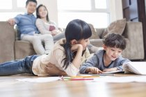 Frères et sœurs chinois étudient ensemble au sol avec les parents sur le canapé regardant — Photo de stock