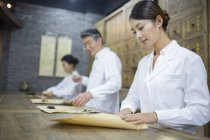 Chinese doctors packing herbs in traditional pharmacy — Stock Photo
