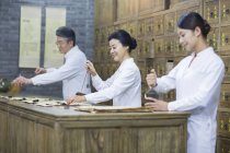Китайские врачи, работающие в традиционных аптека — стоковое фото