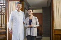 Старший китайський лікаря і зрілі жінки пацієнта в коридорі — стокове фото