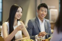 Chinese couple having dinner with friends — Stock Photo