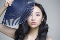 Chinese woman covering face with folding fan — Stock Photo