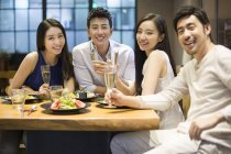 Chinese friends sitting in restaurant together — Stock Photo