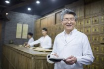 Chinese senior man holding book in traditional pharmacy — Stock Photo