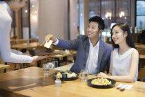 Couple chinois donnant serveuse carte de crédit au restaurant — Photo de stock