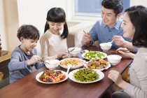 Chinese family eating at dining table together — Stock Photo