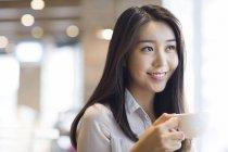 Donna cinese che beve caffè nel caffè — Foto stock