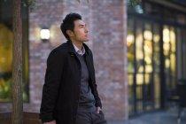 Uomo cinese pensieroso in piedi sulla strada e guardando in alto — Foto stock