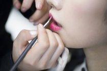 Truccatore applicando il rossetto alle labbra della giovane donna — Foto stock