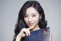Chinese woman posing with folding fan — Stock Photo