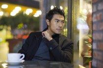 Homme chinois pensif assis au café rue — Photo de stock