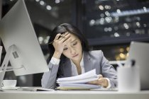 Chinese businesswoman working late with documents in office — Stock Photo