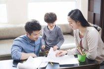 Китайские родители, помогая сына с заданием — стоковое фото