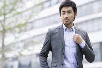 Confident chinese businessman standing on street — Stock Photo