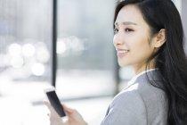 Empresaria China holding smartphone y mirando lejos - foto de stock
