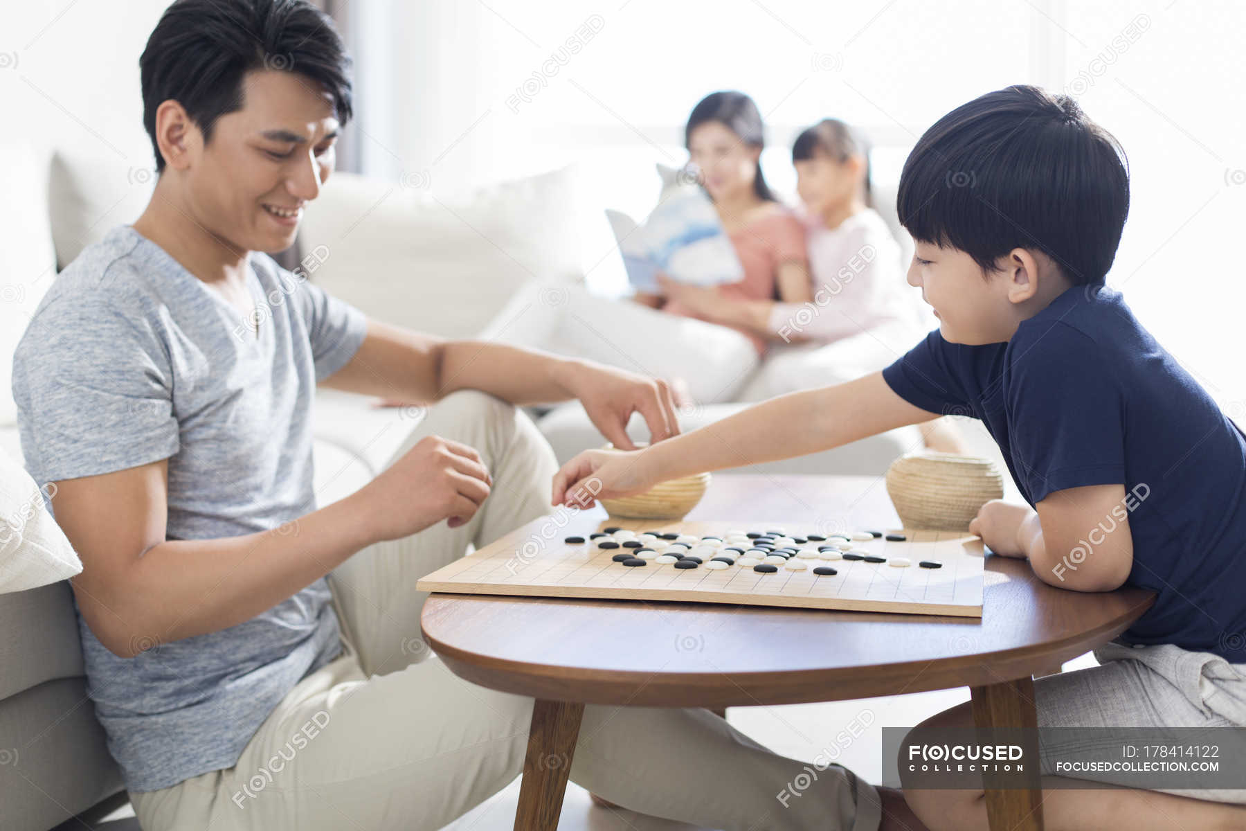 Chinese Boy Playing Game Of Go With Father While Mother And