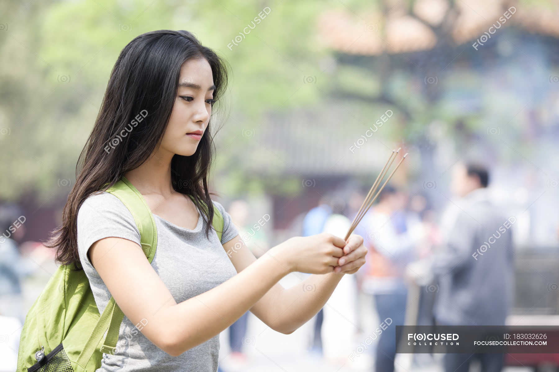 72d99ce3ae Chinese woman burning incense in Lama Temple — selective focus ...
