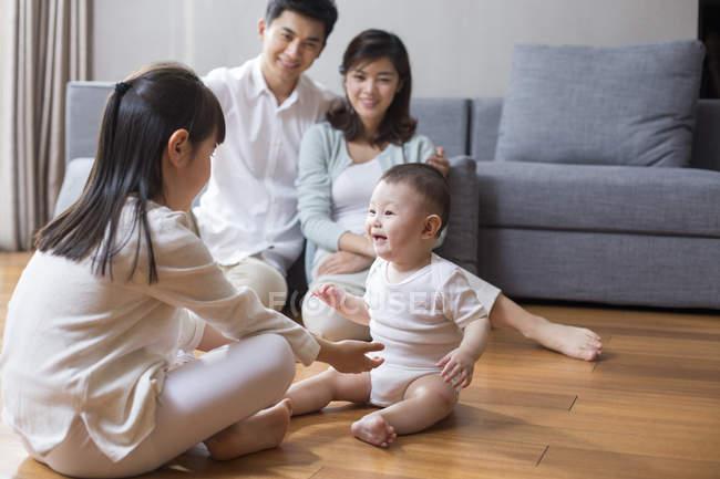 Famiglia cinese che si siede sul pavimento in legno nel soggiorno ...