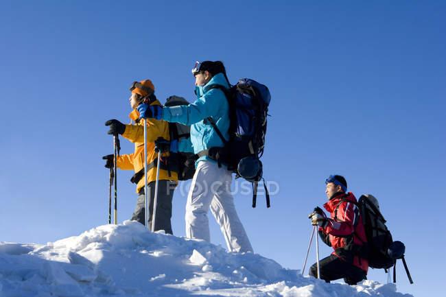 Три китайских лыжников, походы в горы со снежными вершинами — стоковое фото