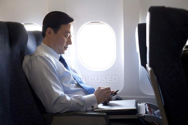 Empresário chinês trabalhando com smartphone no avião — Fotografia de Stock