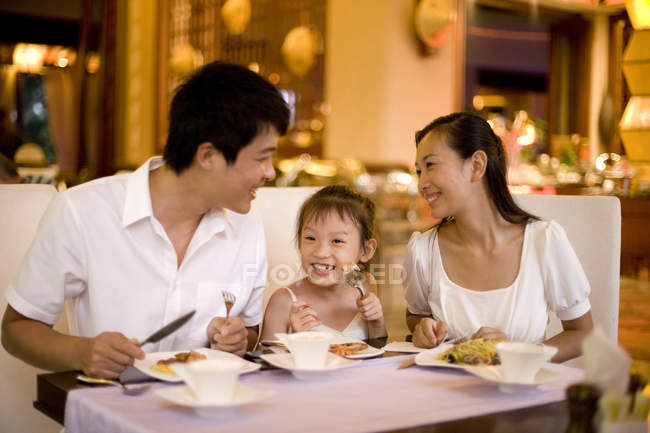 Chinese family with daughter dining at restaurant — Stock Photo