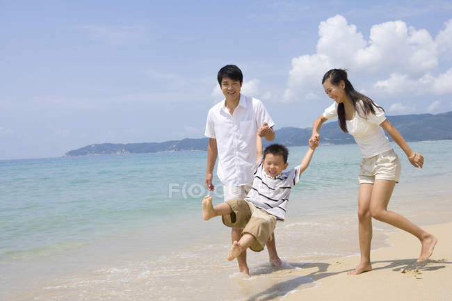Parents holding swinging son on beach — Stock Photo