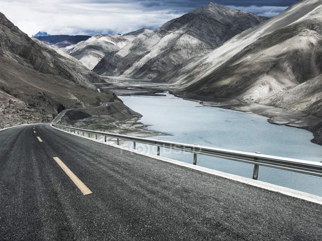Winding road and lake in Tibet mountains, China — Stock Photo
