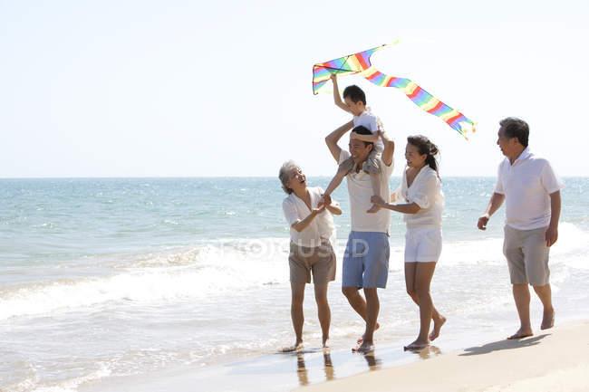 Chinesischer Junge mit Drachen auf den Schultern des Vaters spaziert mit Familie am Strand — Stockfoto