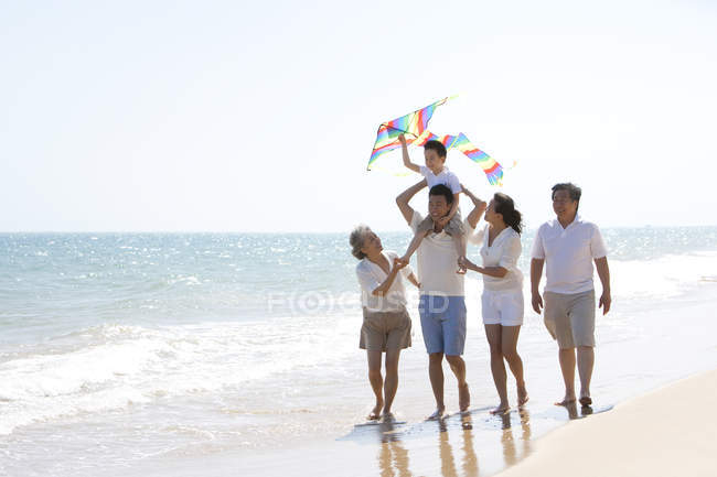 Китайський хлопчик з кайт на плечах батько прогулянки з родиною на пляжі — стокове фото