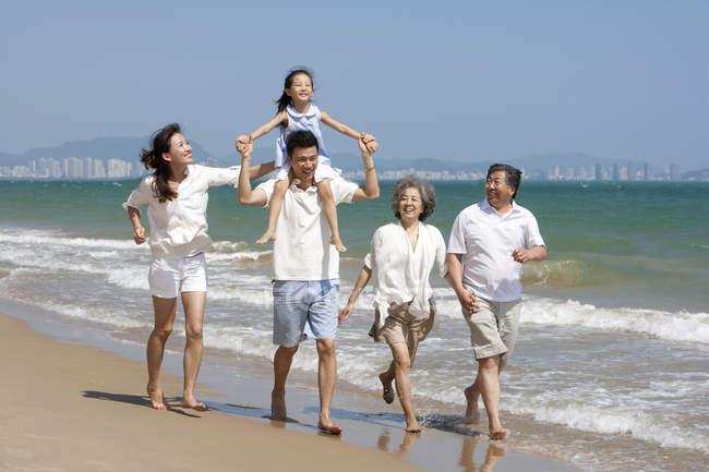 China chica sobre los hombros del padre caminando con la familia en la playa - foto de stock