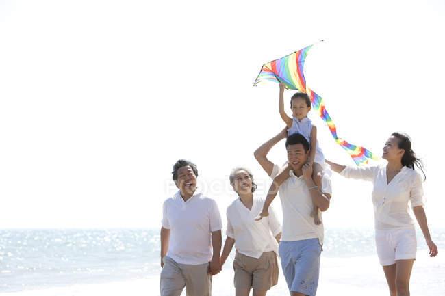 Menina chinesa com pipa nos ombros do pai andando com a família na praia — Fotografia de Stock