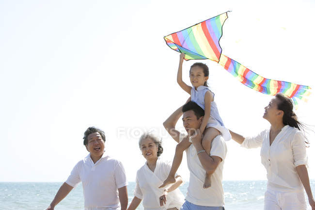 Chinese girl with kite on father shoulders walking with family on beach — Stock Photo