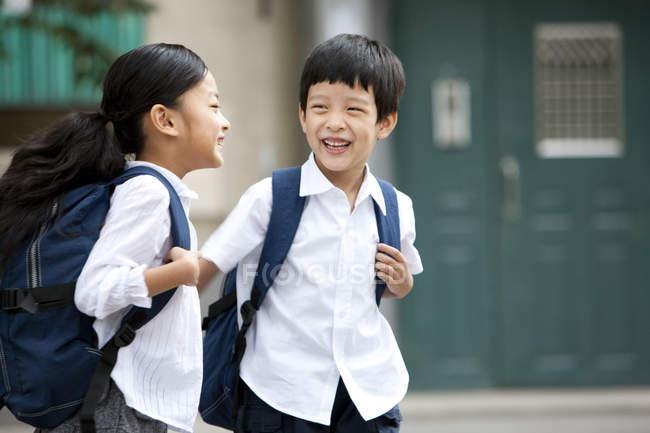 Crianças chinesas com mochilas rindo na rua — Fotografia de Stock