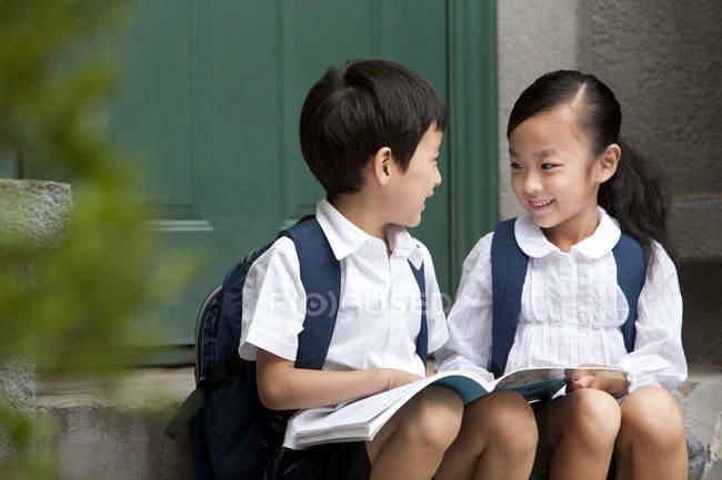 Chinês menino e menina com livro falando na varanda — Fotografia de Stock