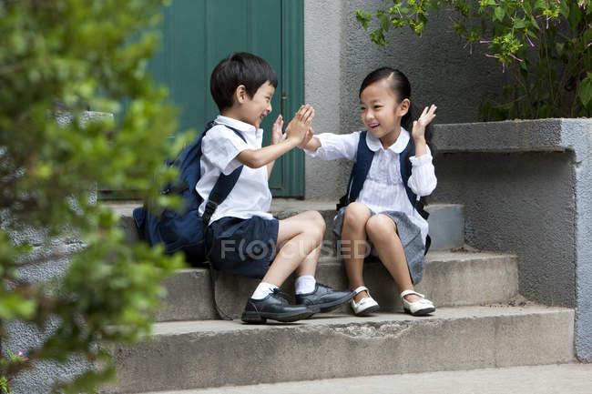 Китайские школьники играют на ступеньках — стоковое фото