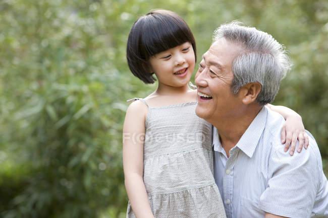 Chinesischer Opa und Enkelin umarmen und lachen im Garten — Stockfoto