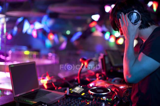 Male DJ doing record scratching in nightclub — Stock Photo