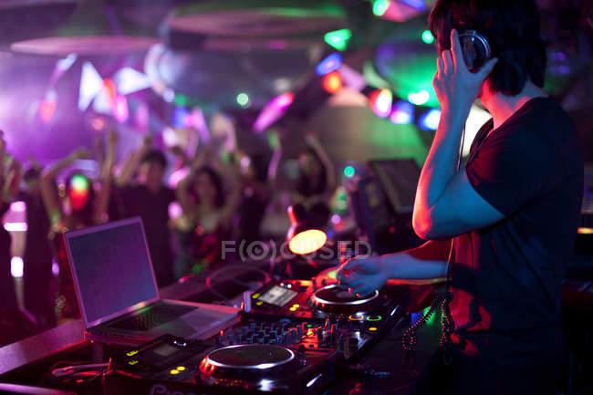 Male DJ doing record scratching in nightclub — Stock Photo