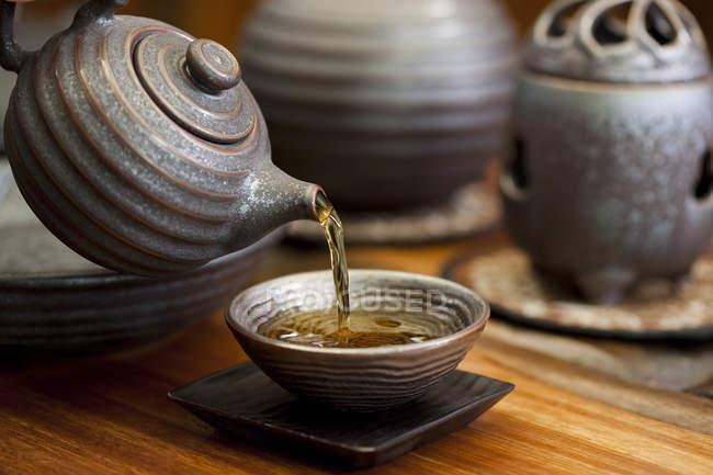 Versant de théière chinoise dans la tasse de thé — Photo de stock