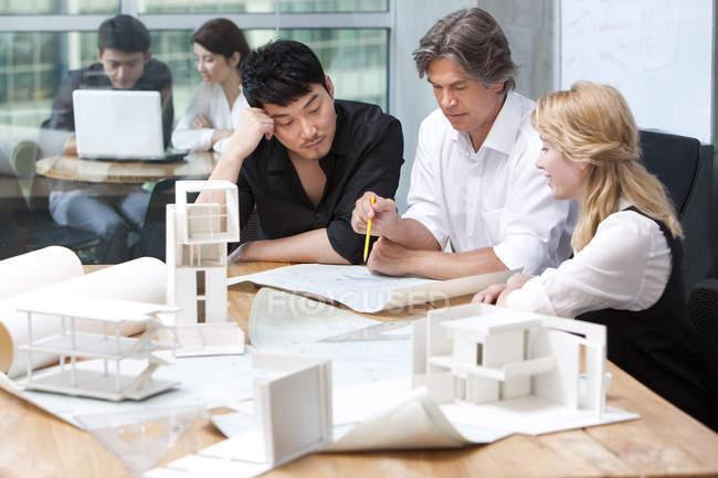 Equipo de arquitectos trabajando en planos - foto de stock