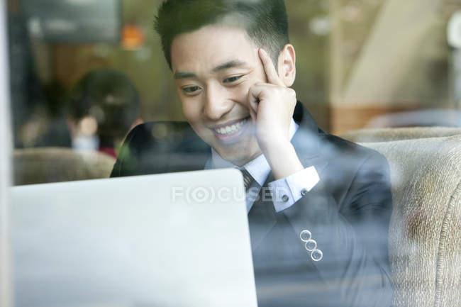 Uomo d'affari cinese utilizzando computer portatile nella caffetteria e sorridente — Foto stock