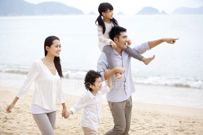 Chinese family strolling on beach and pointing at view — Stock Photo