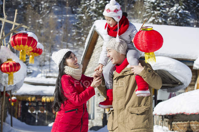 Chinese father carrying daughter with lantern on shoulders while mother watching — Stock Photo