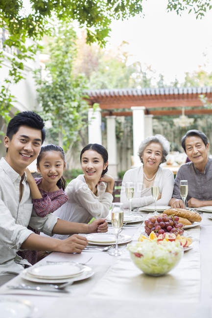 Chinese multi-generation family sitting at dining table in courtyard — Stock Photo