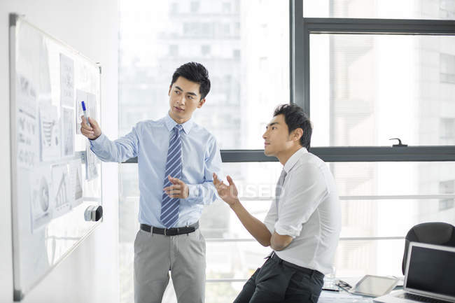 Chinese businessmen talking in board room — Stock Photo