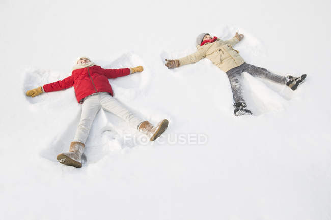 Chinese children making snow angels — Stock Photo