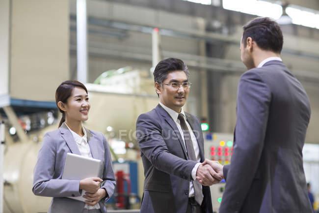 Бизнесмены пожимают руки на промышленном заводе — стоковое фото