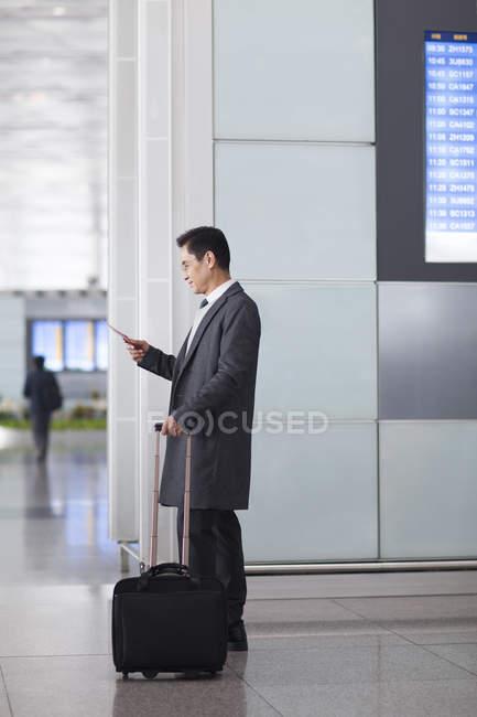 Азиатский мужчина, использующий смартфон с ручной клади в вестибюле аэропорта — стоковое фото